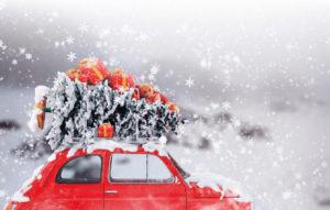 Kuvassa on punainen volkkari, joka kiitää eteenpäin lumisateessa joulukuusi ja lahjapaketteja katolla.