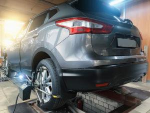 Autokorjaamossa harmaan henkilöauton vasemmassa takapyörässä on ohjauskulmien eli aurauskulmien säätölaite, joka mittaa kulmien lukemia.