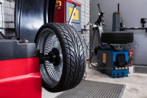 Renkaiden tasapainotus, Autokorjaamolla tasapainotettava rengas on punaisen alustan päällä valmiina pyöritettäväksi.