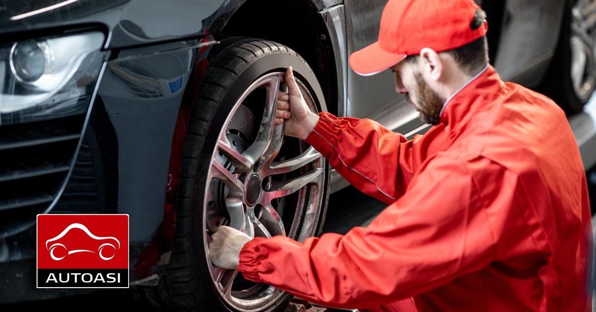 Asentaja irrottaa tummapintaisen auton rengasta vanteesta, renkaiden vaihto, rengashotelli ja renkaiden tasapainotus, CGS autohuolto Kirkkonummi
